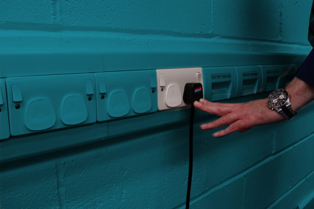 Person pushing plug into a plug socket