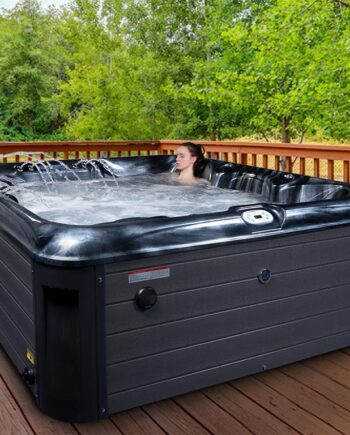 woman relaxing outdoors in garden in a hot tub on the decking