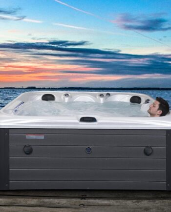 Man relaxing in a luxury hot tub on decking by a lake