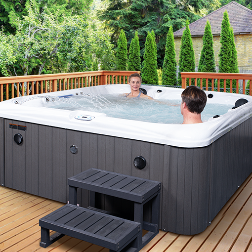 Couple relaxing in hot tub outdoors in the garden on the decking