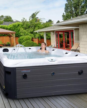 Woman in luxury six person hot tub outside on decking in garden